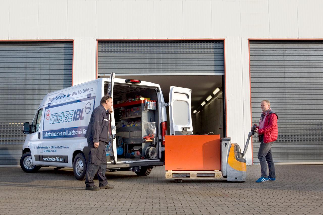 Auf diesem Foto sind zwei Mitarbeiter der Firma Knabe IBL – Industriebatterien und Ladetechnik GmbH zu sehen, wie sie eine Batterie verladen.